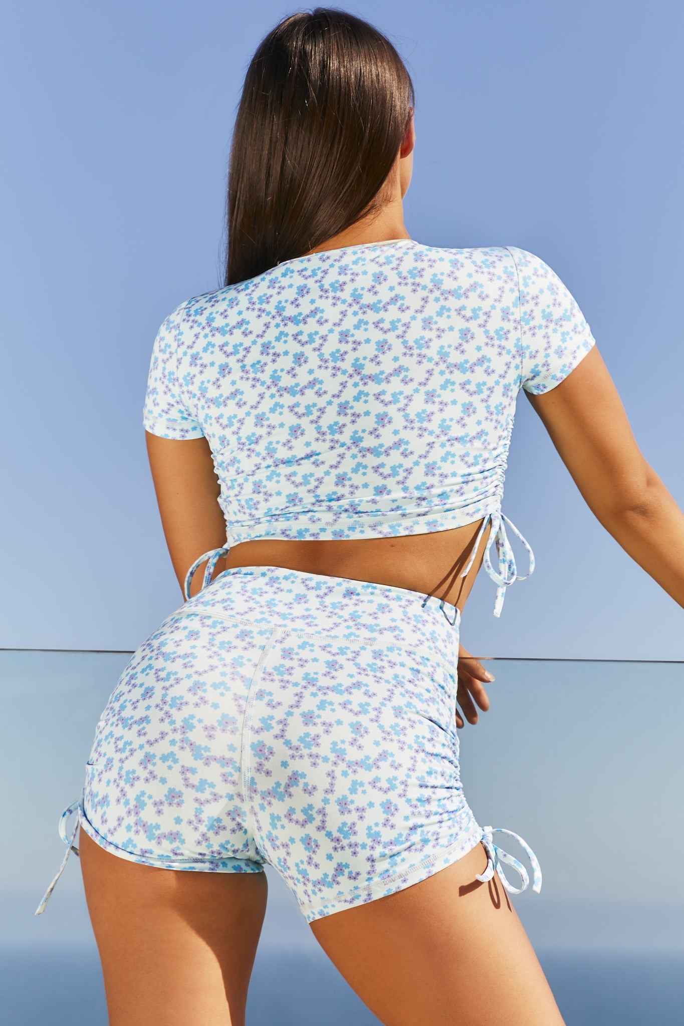 Blue floral print slinky round neck short sleeve crop top with ruched side seams. Image 3 of 6.