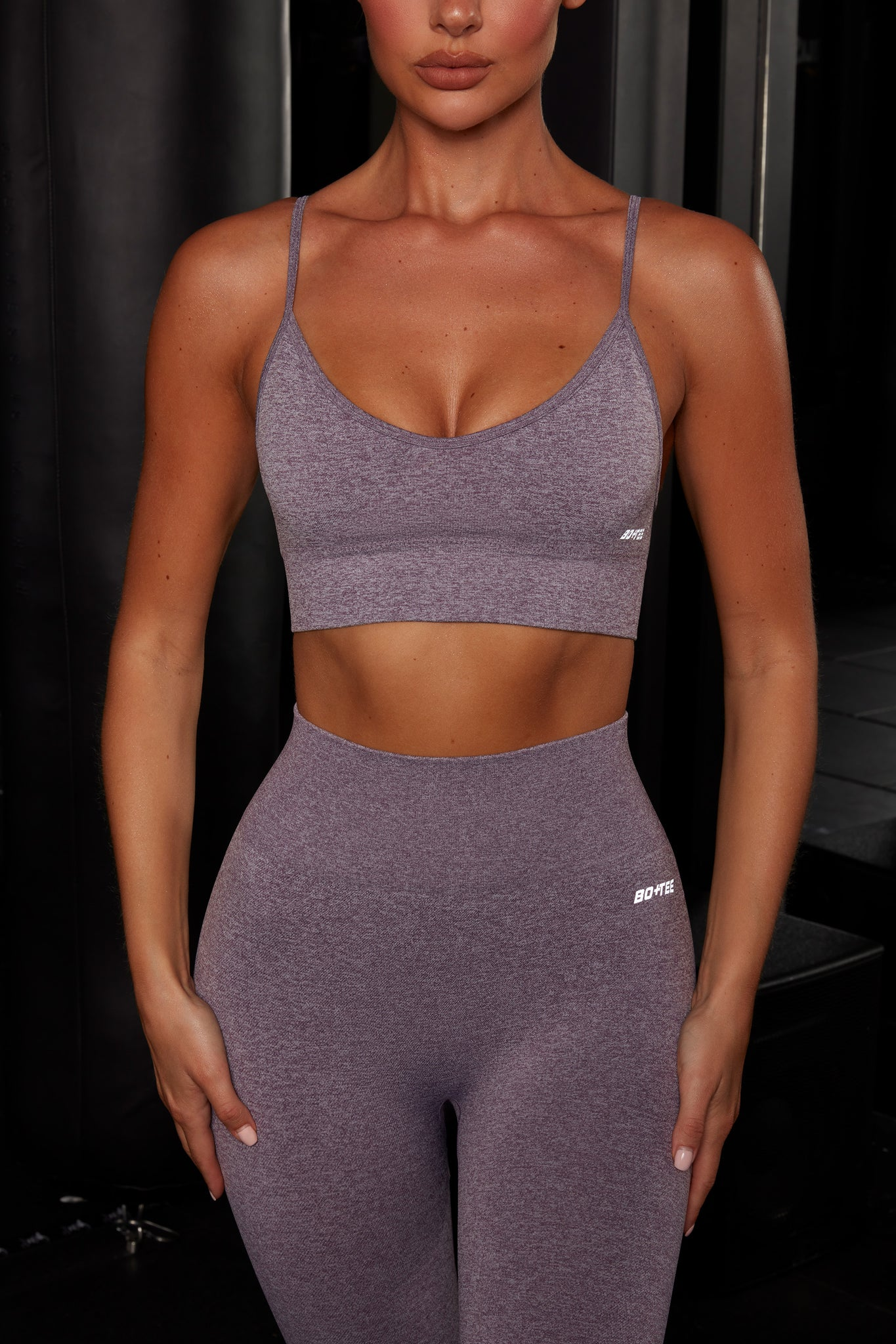 Plain purple melange V neck sports bra with ribbed underband, reflective branding and thin adjustable straps. Image 1 of 6.