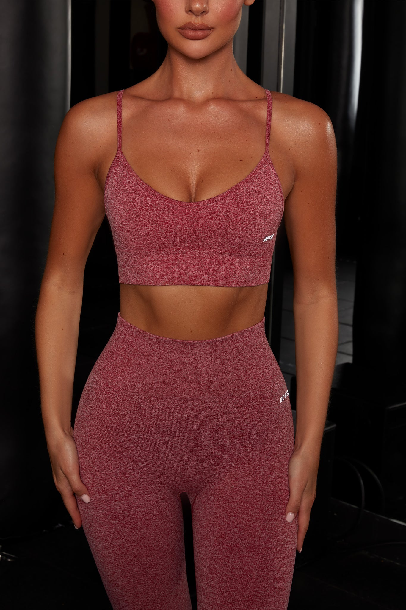 Plain red melange V neck sports bra with ribbed underband, reflective branding and thin adjustable straps. Image 4 of 6.