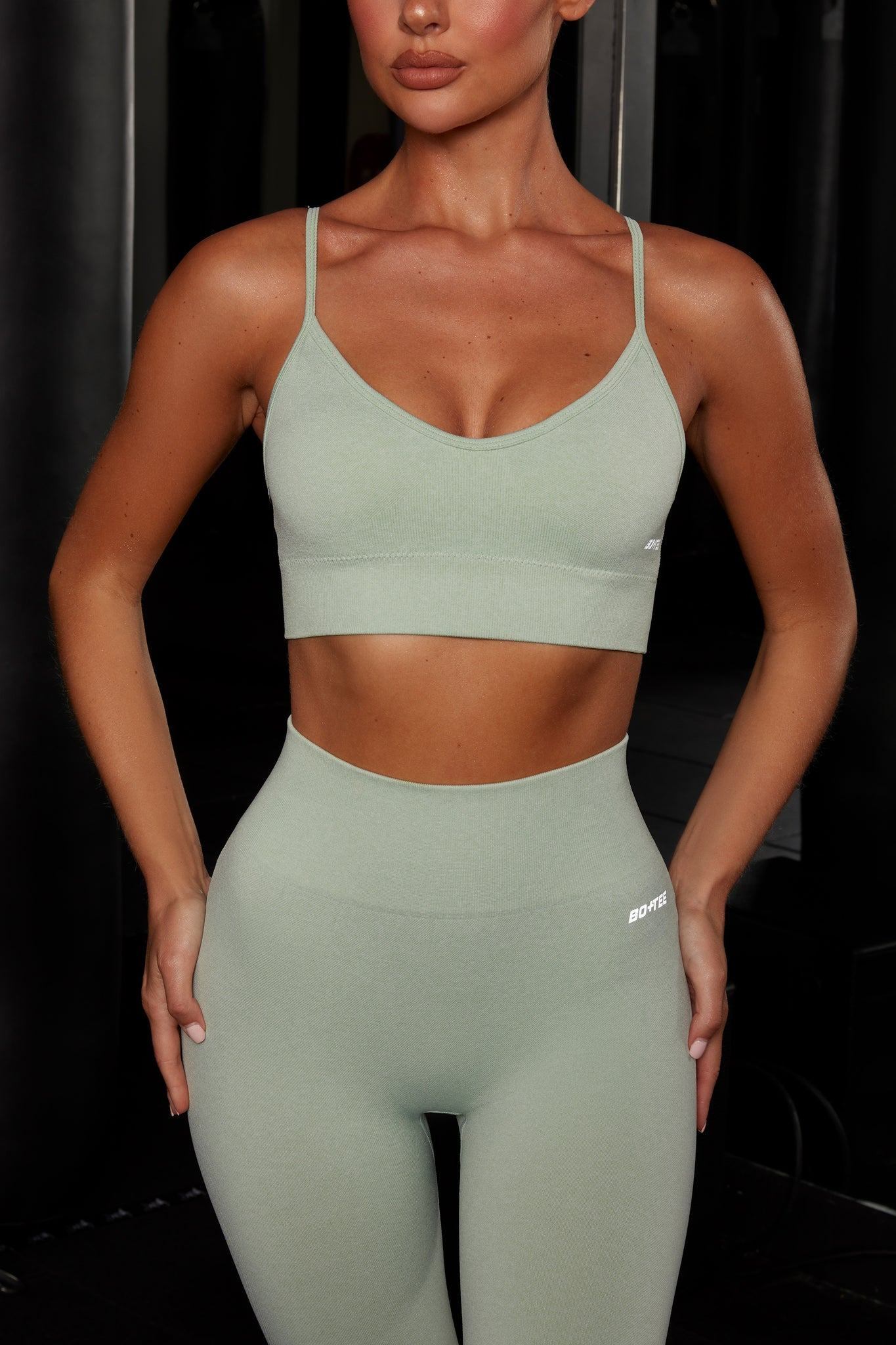 Plain light green melange V neck sports bra with ribbed underband, reflective branding and thin adjustable straps. Image 4 of 6.