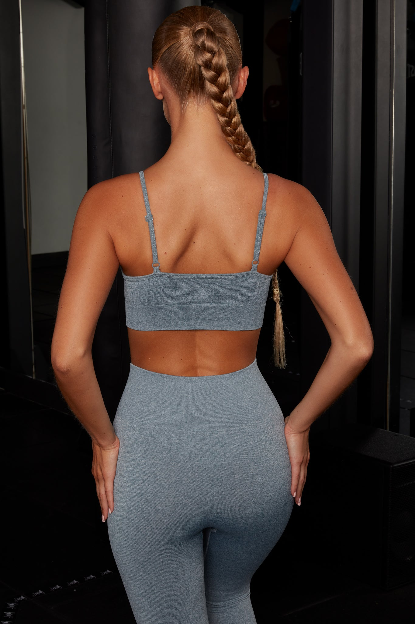 Plain blue melange V neck sports bra with ribbed underband, reflective branding and thin adjustable straps. Image 3 of 6.