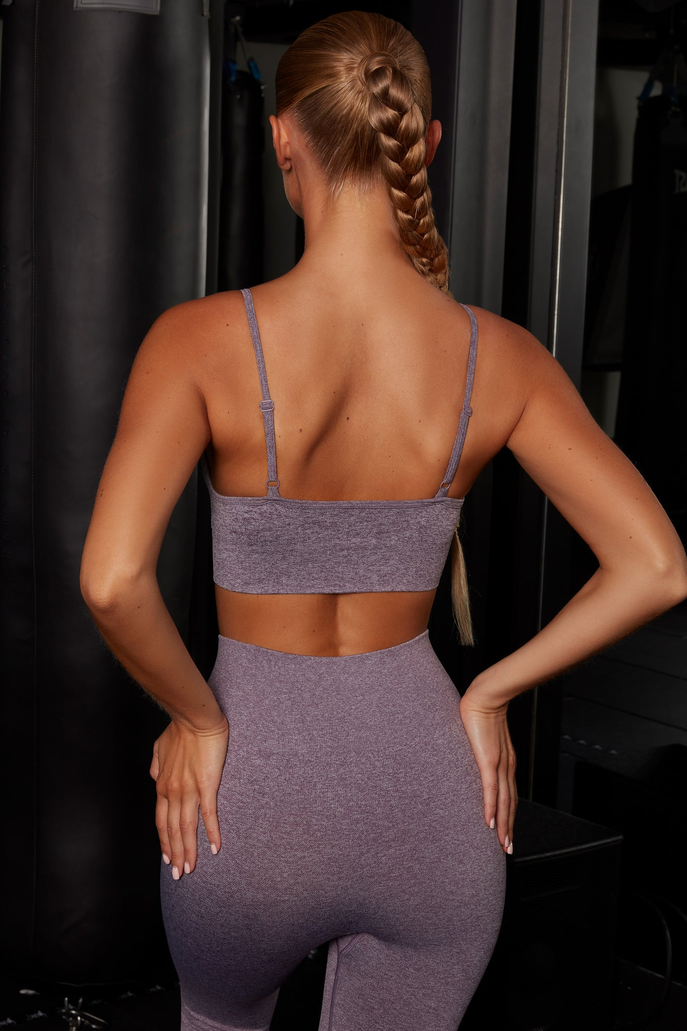 Plain purple melange V neck sports bra with ribbed underband, reflective branding and thin adjustable straps. Image 3 of 6.