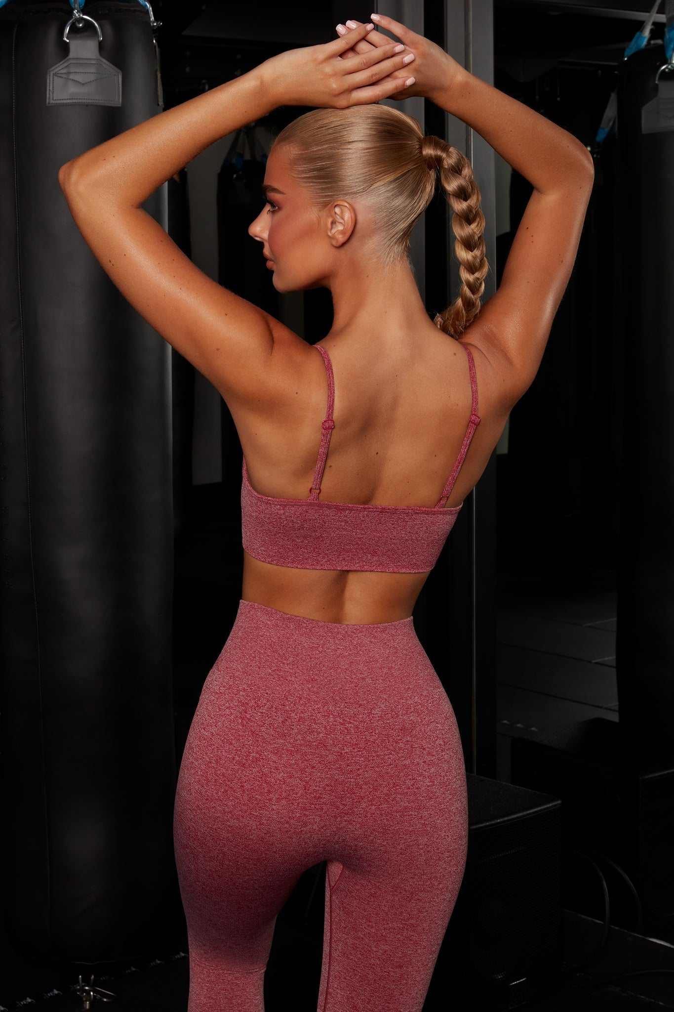 Plain red melange V neck sports bra with ribbed underband, reflective branding and thin adjustable straps. Image 3 of 6.