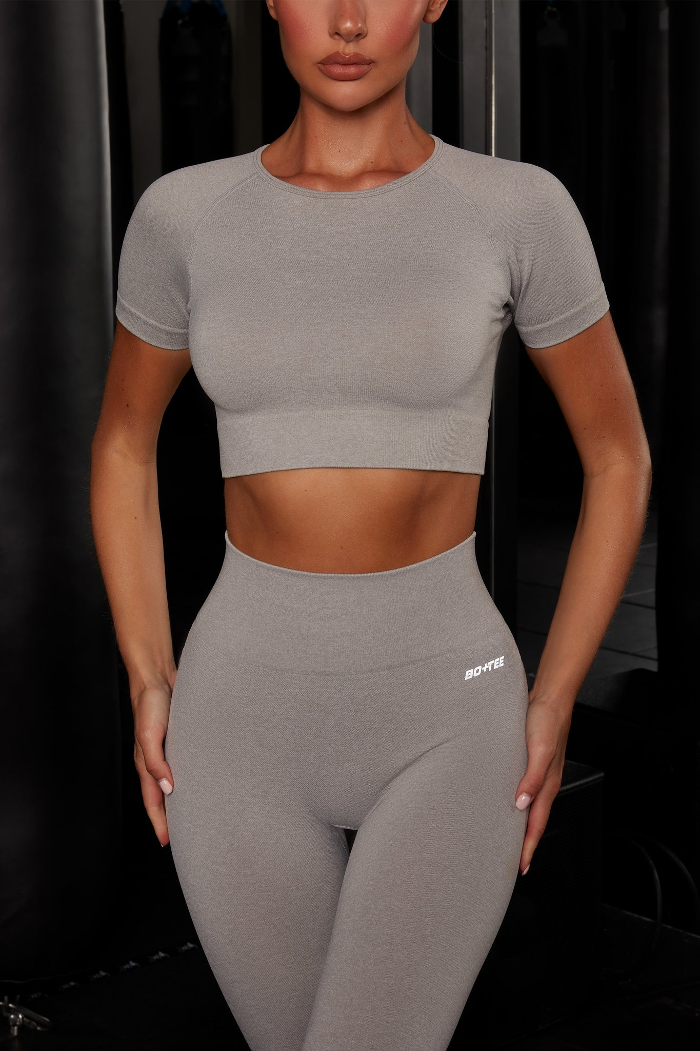Plain light grey melange round neck crop top with ribbed underband, reflective branding and short sleeves. Image 4 of 6.