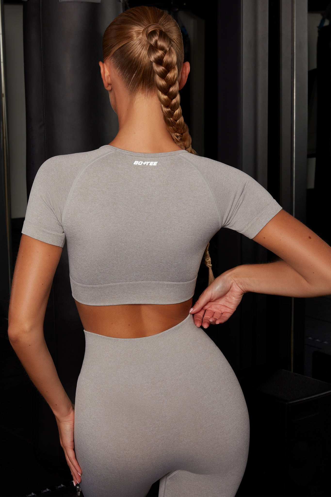 Plain light grey melange round neck crop top with ribbed underband, reflective branding and short sleeves. Image 3 of 6.