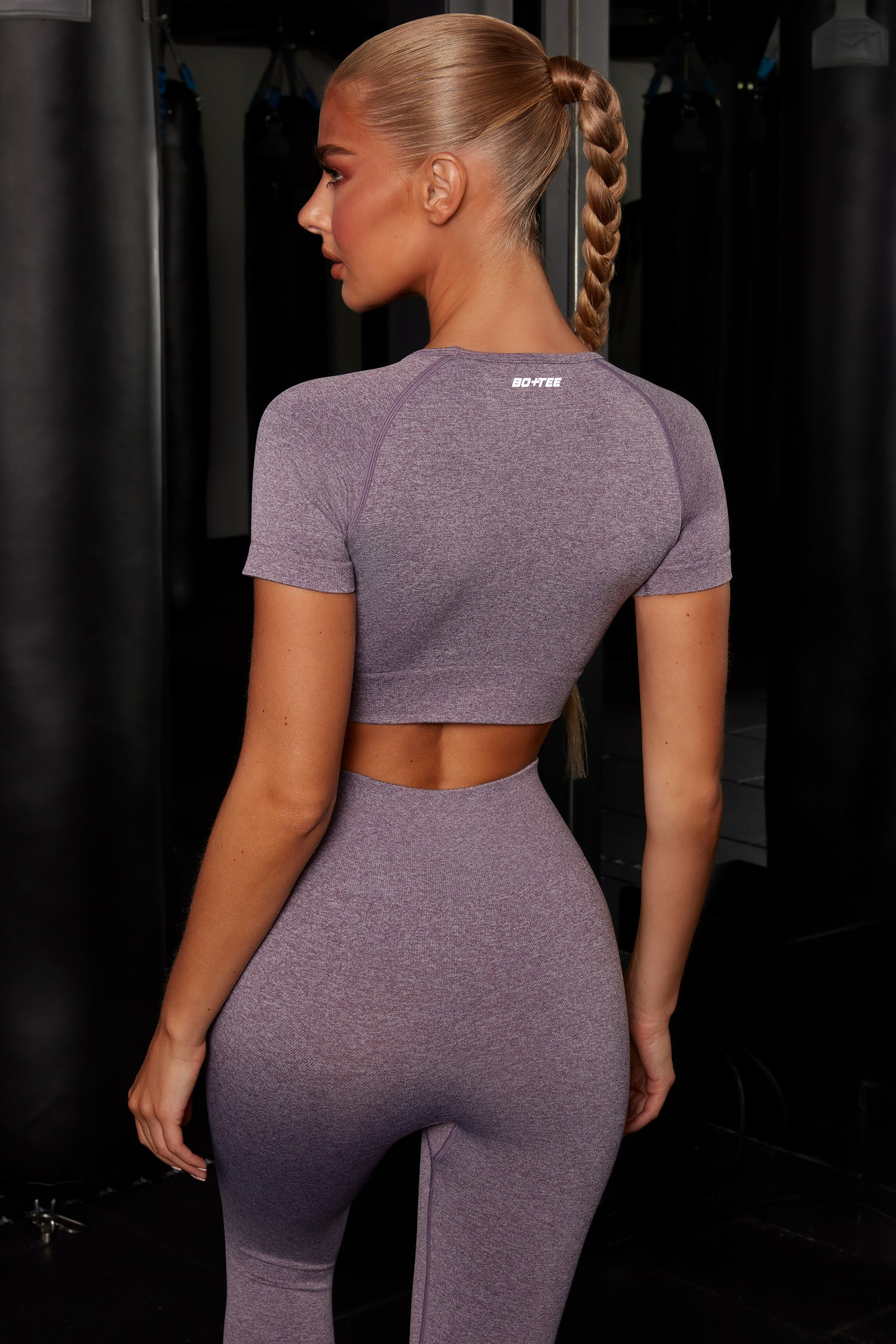 Plain purple melange round neck crop top with ribbed underband, reflective branding and short sleeves. Image 3 of 6.