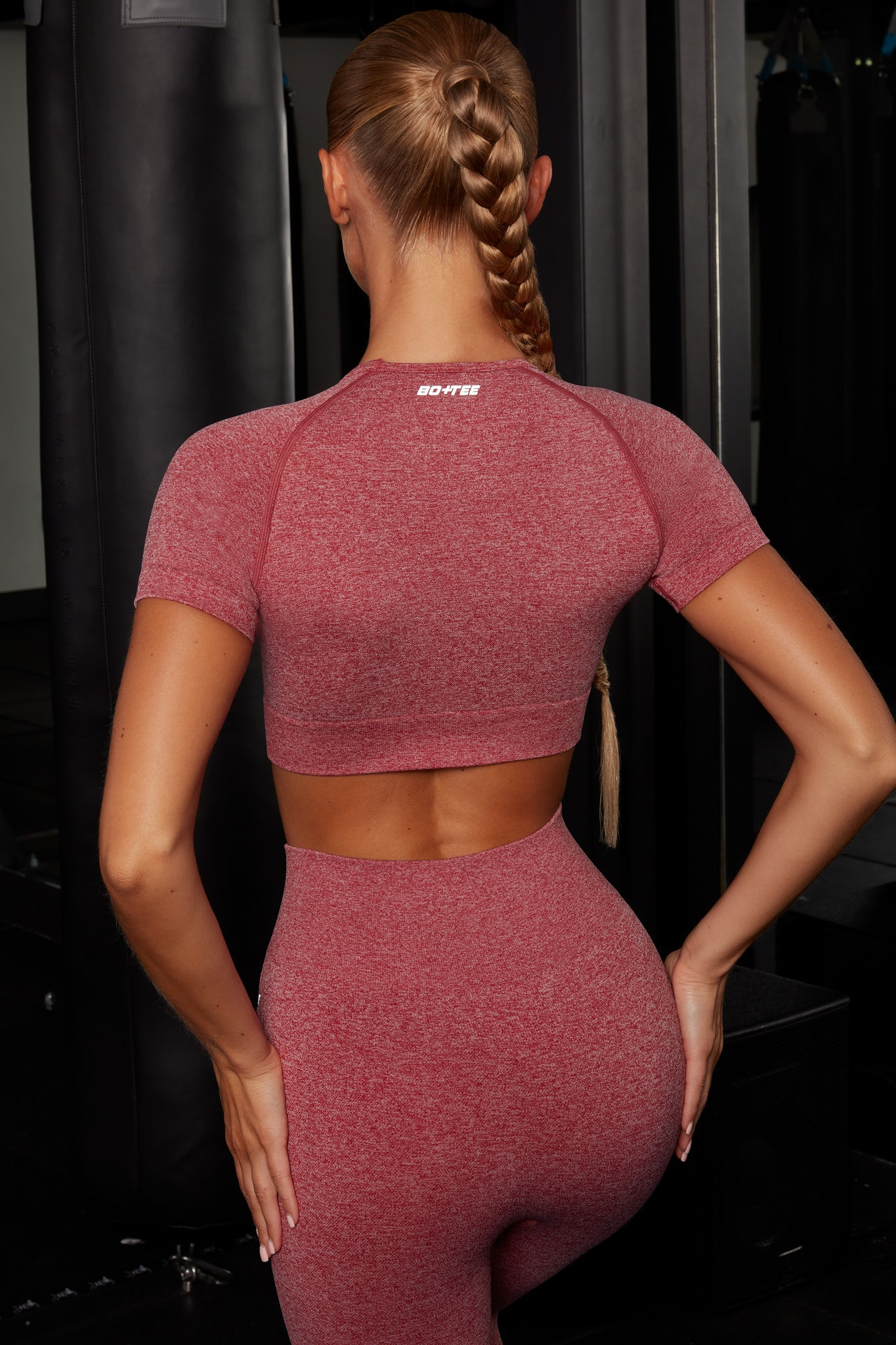 Plain red melange round neck crop top with ribbed underband, reflective branding and short sleeves. Image 3 of 6.