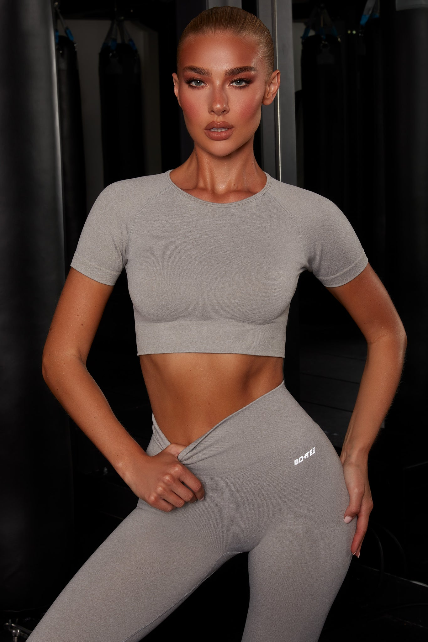 Plain light grey melange round neck crop top with ribbed underband, reflective branding and short sleeves. Image 1 of 6.