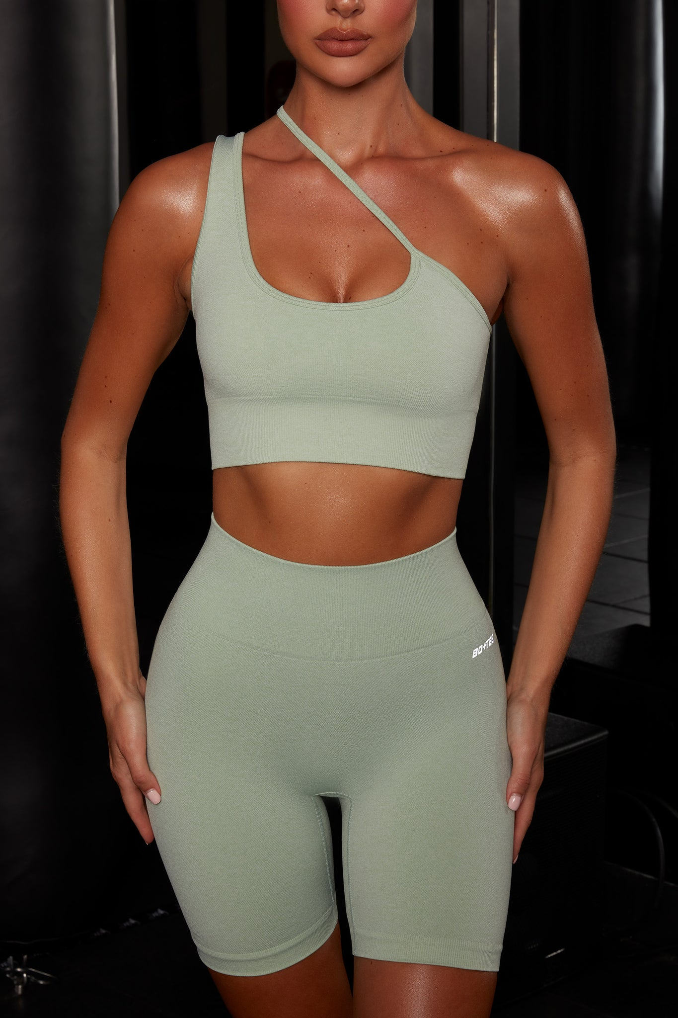 Plain green crop top with asymmetric strap. Image 1 of 6.