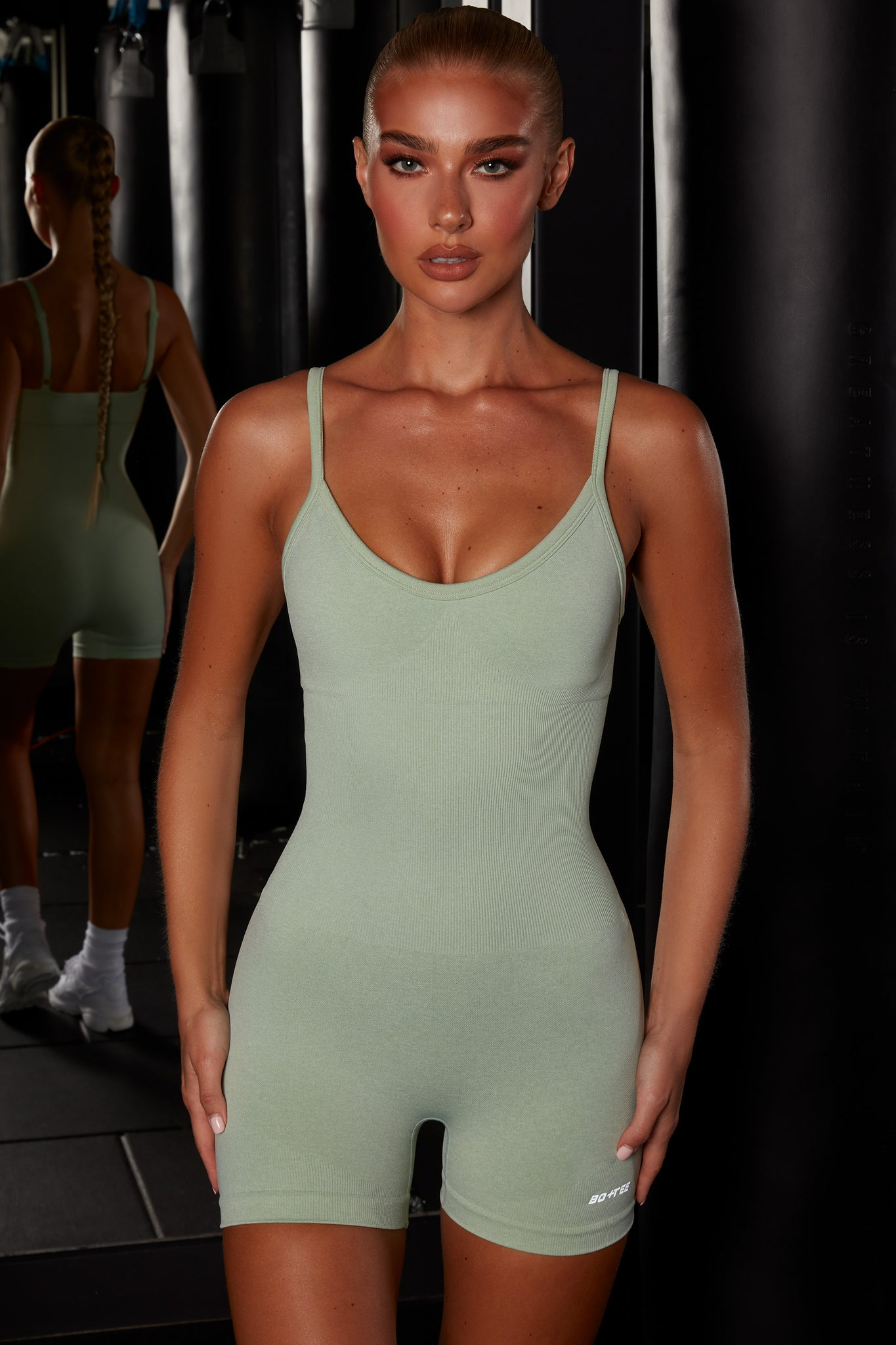 Plain green seamless unitard with plunge neck and adjustable straps. Image 1 of 6.