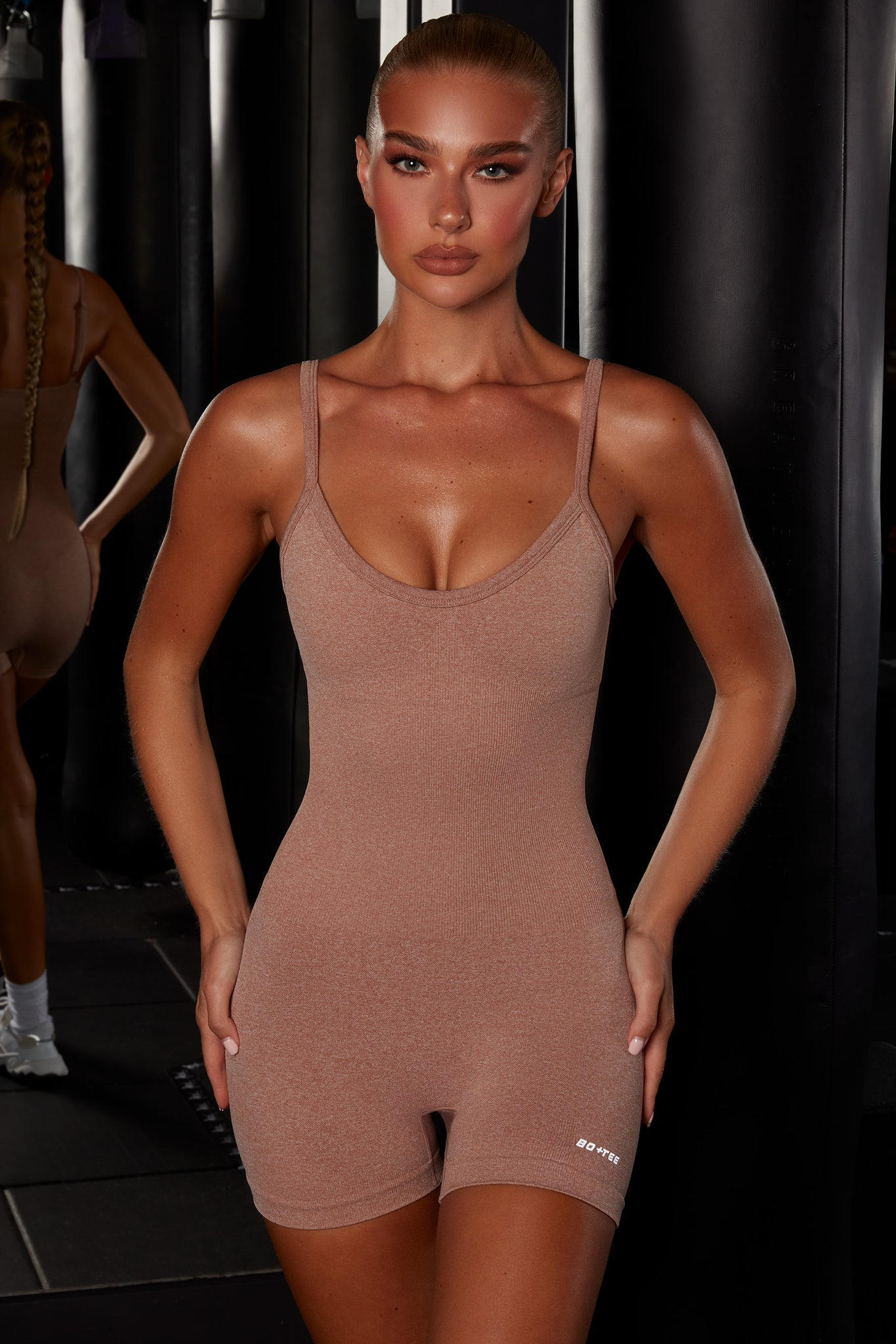 Plain brown seamless unitard with plunge neck and adjustable straps. Image 1 of 6.