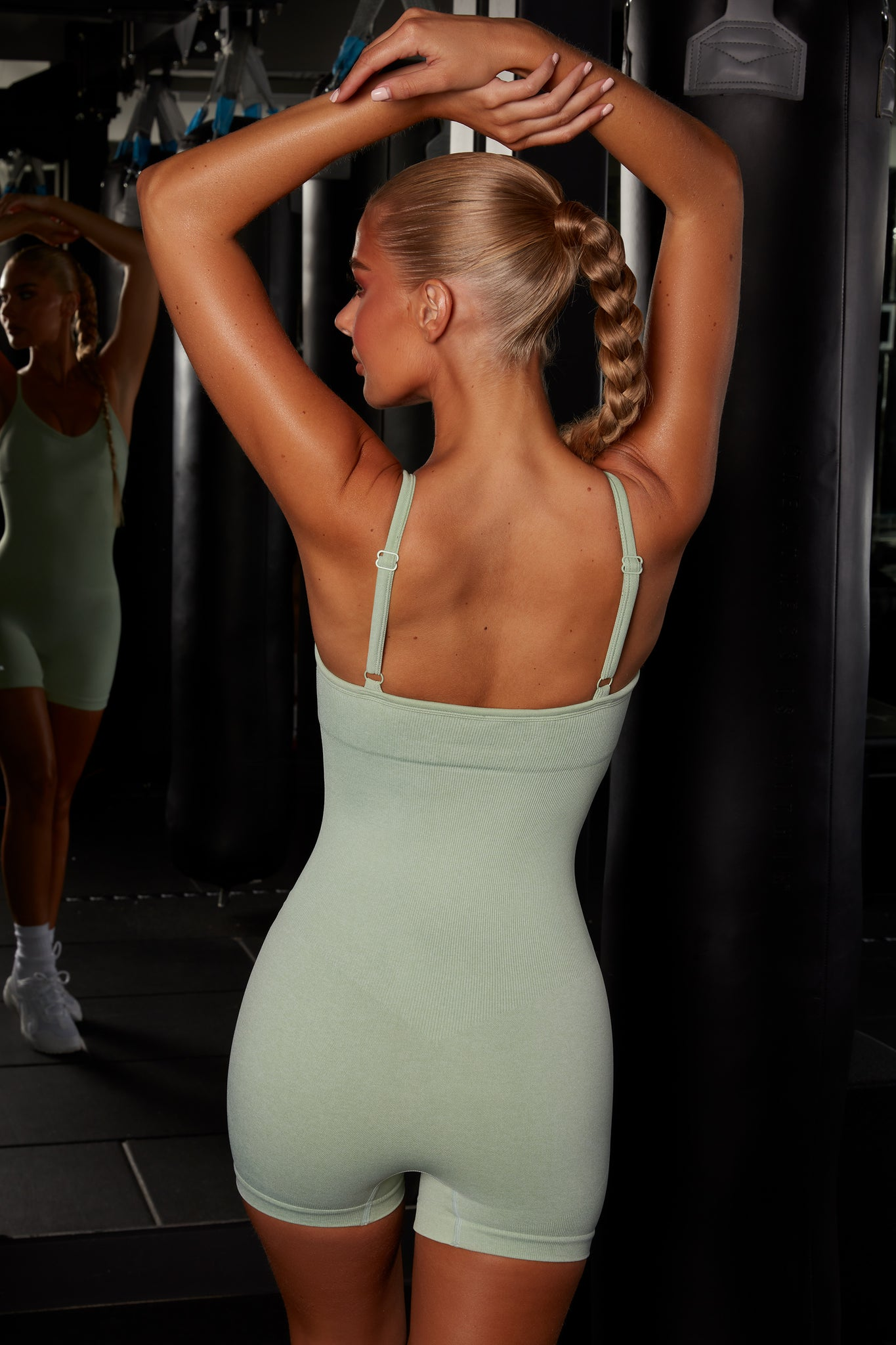 Plain green seamless unitard with plunge neck and adjustable straps. Image 3 of 6.