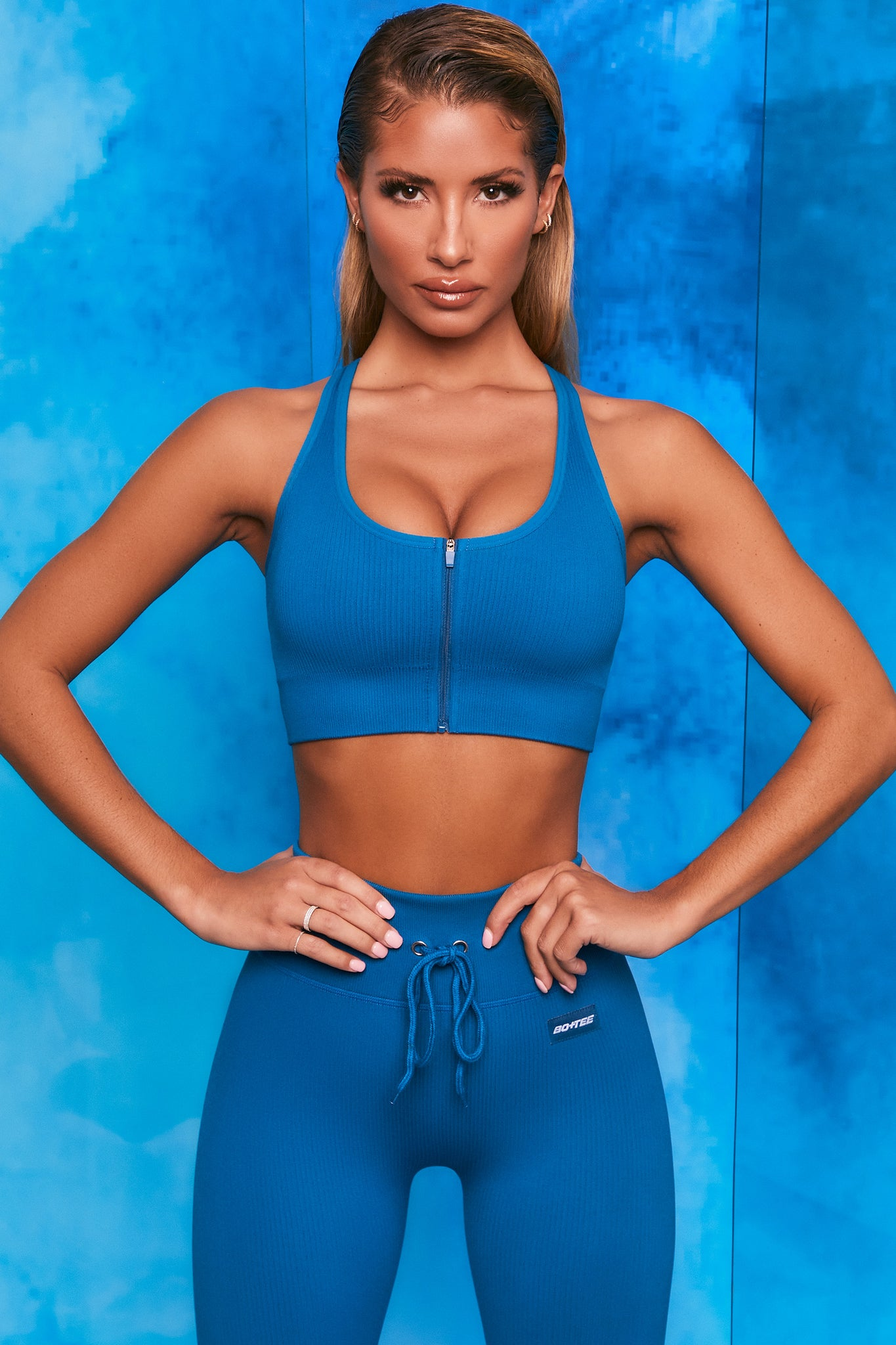 Plain blue ribbed scoop neck sports bra with zip front and racer back. Image 1 of 6