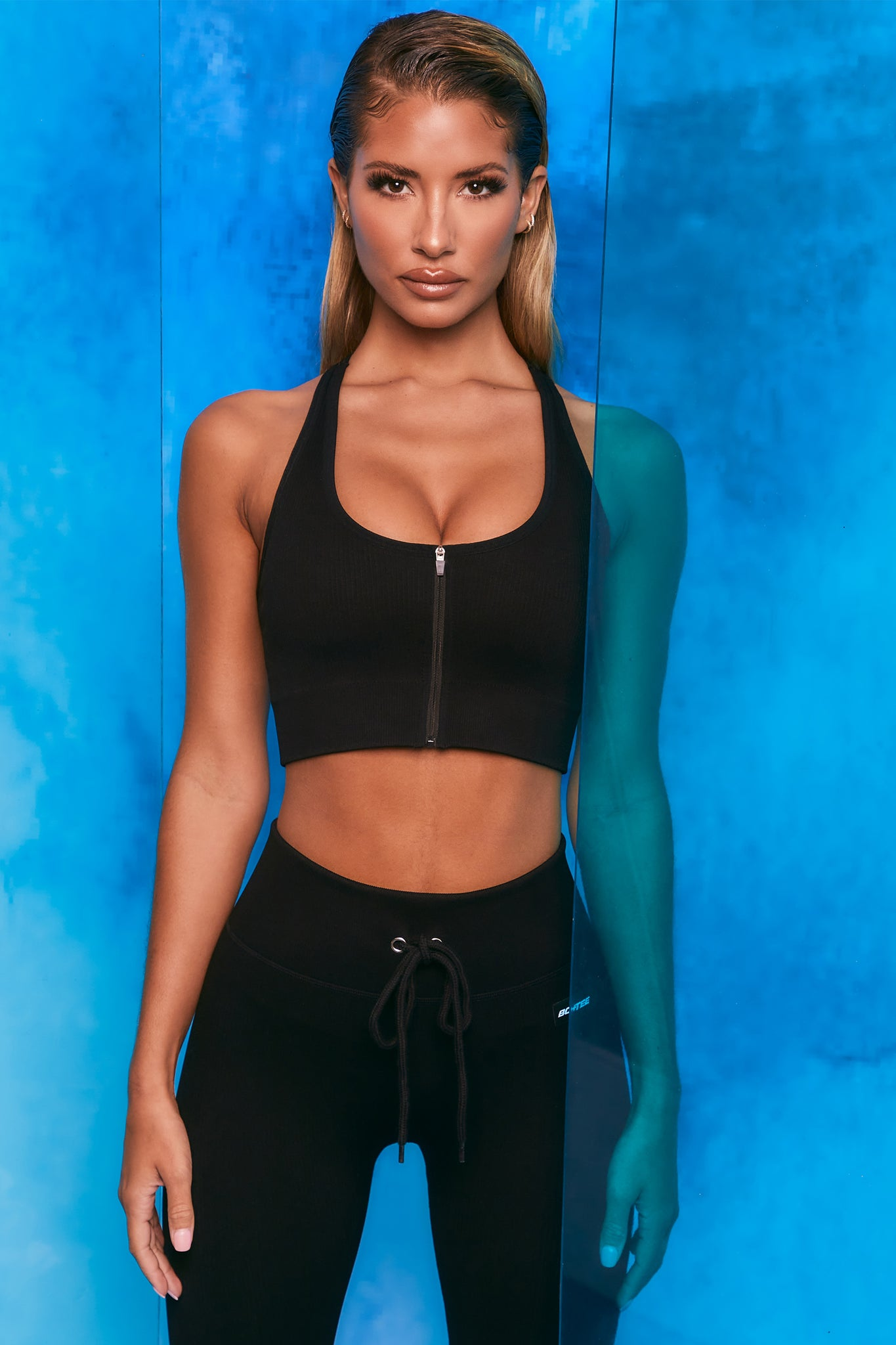 Plain black ribbed scoop neck sports bra with zip front and racer back. Image 1 of 6