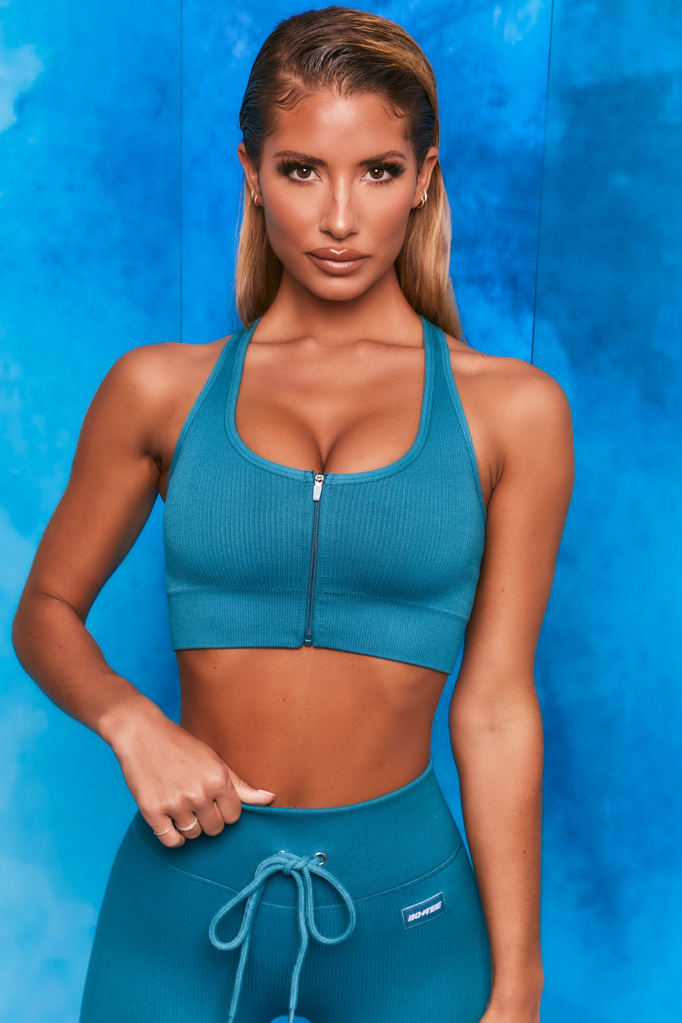 Plain teal ribbed scoop neck sports bra with zip front and racer back. Image 1 of 6