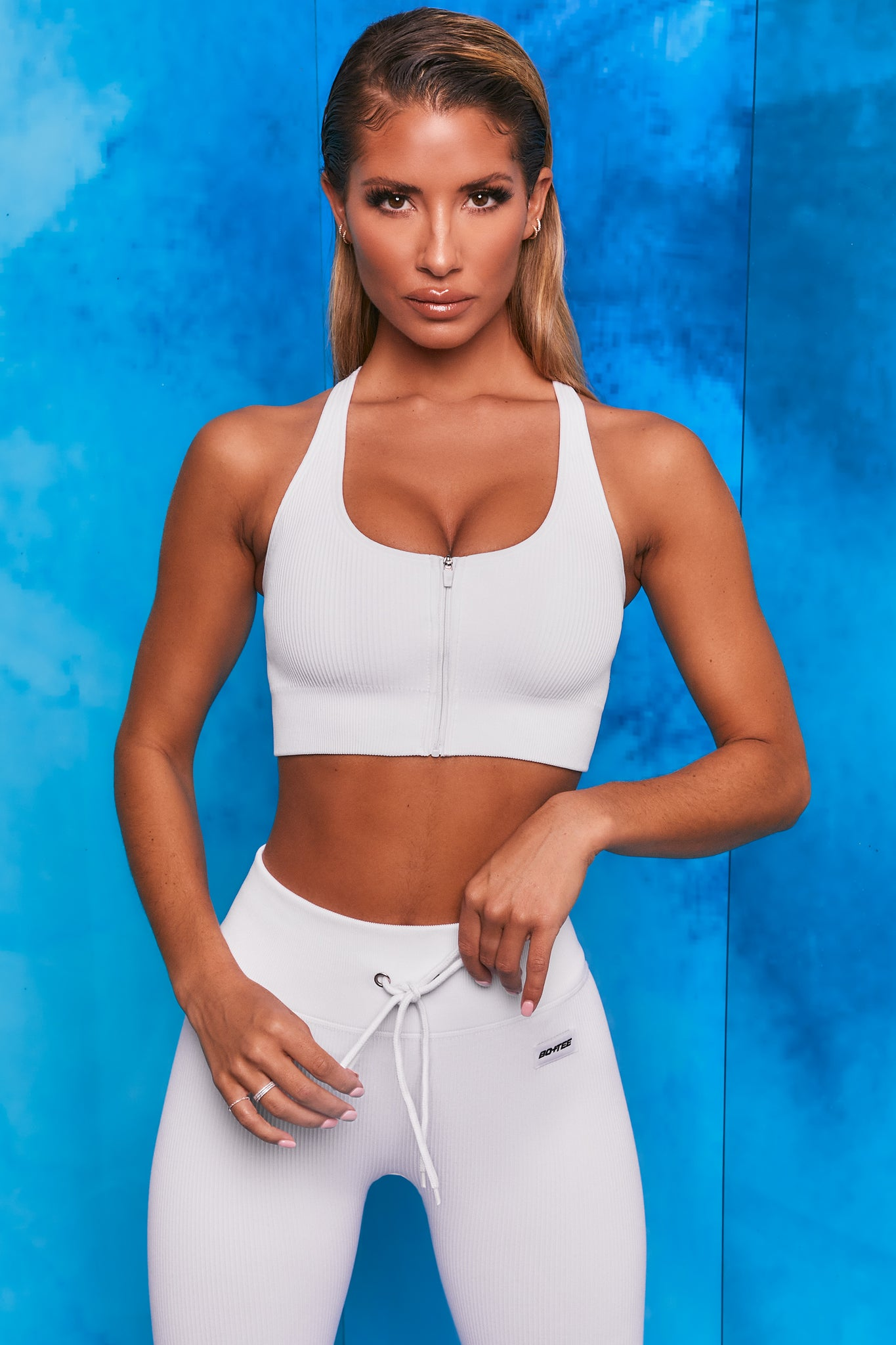 Plain white ribbed scoop neck sports bra with zip front and racer back. Image 1 of 6