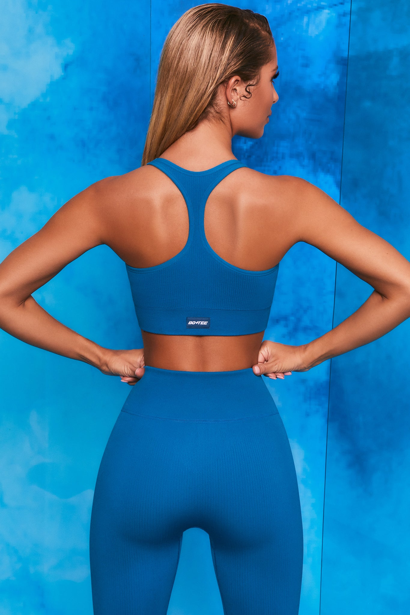 Plain blue ribbed scoop neck sports bra with zip front and racer back. Image 3 of 6