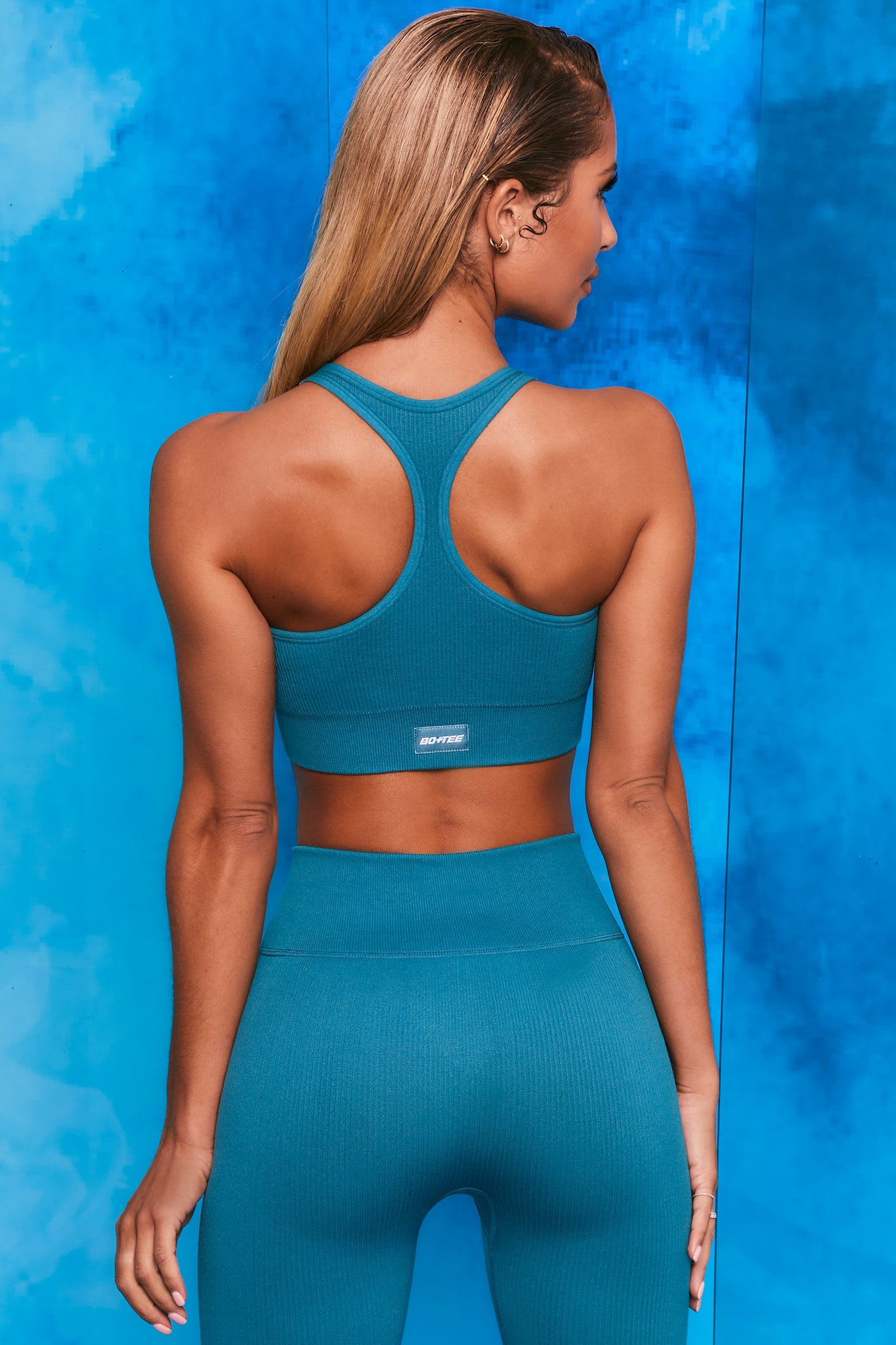 Plain teal ribbed scoop neck sports bra with zip front and racer back. Image 3 of 6