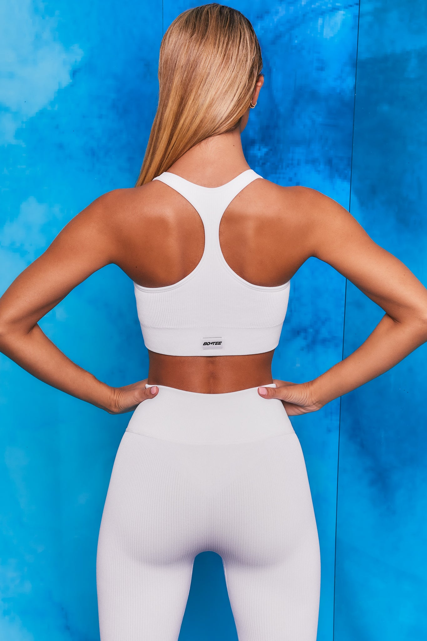 Plain white ribbed scoop neck sports bra with zip front and racer back. Image 3 of 6