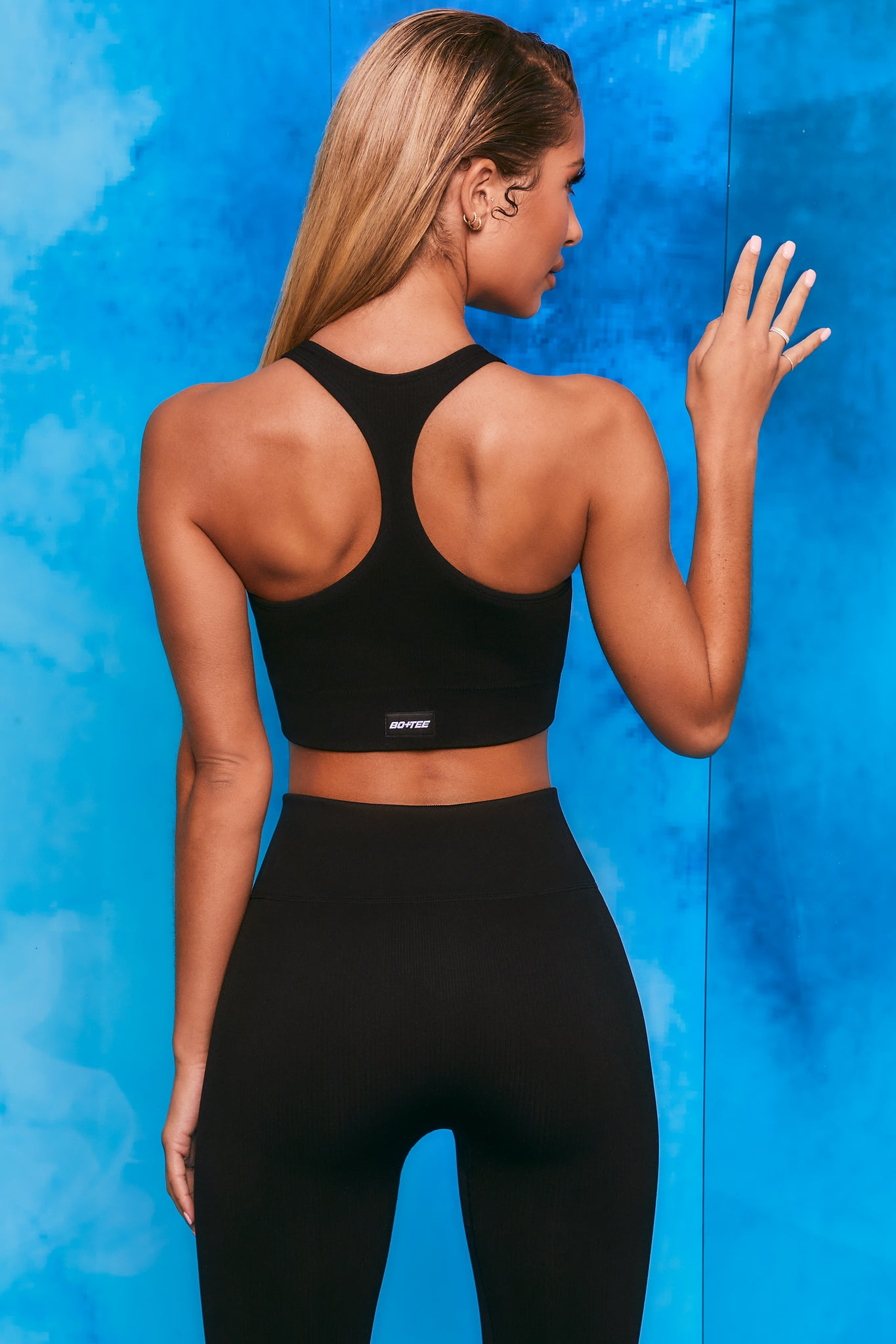 Plain black ribbed scoop neck sports bra with zip front and racer back. Image 3 of 6