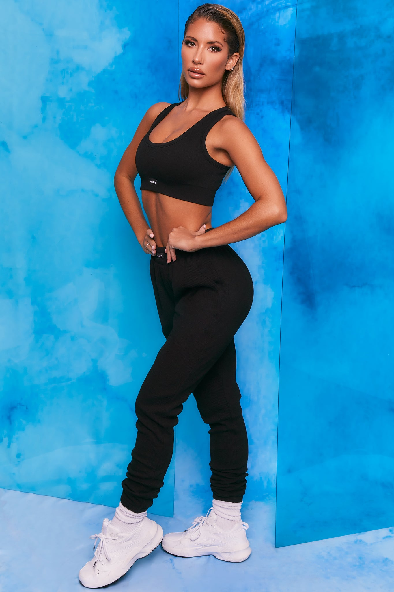 Plain black ribbed scoop neck sports bra. Image 2 of 6