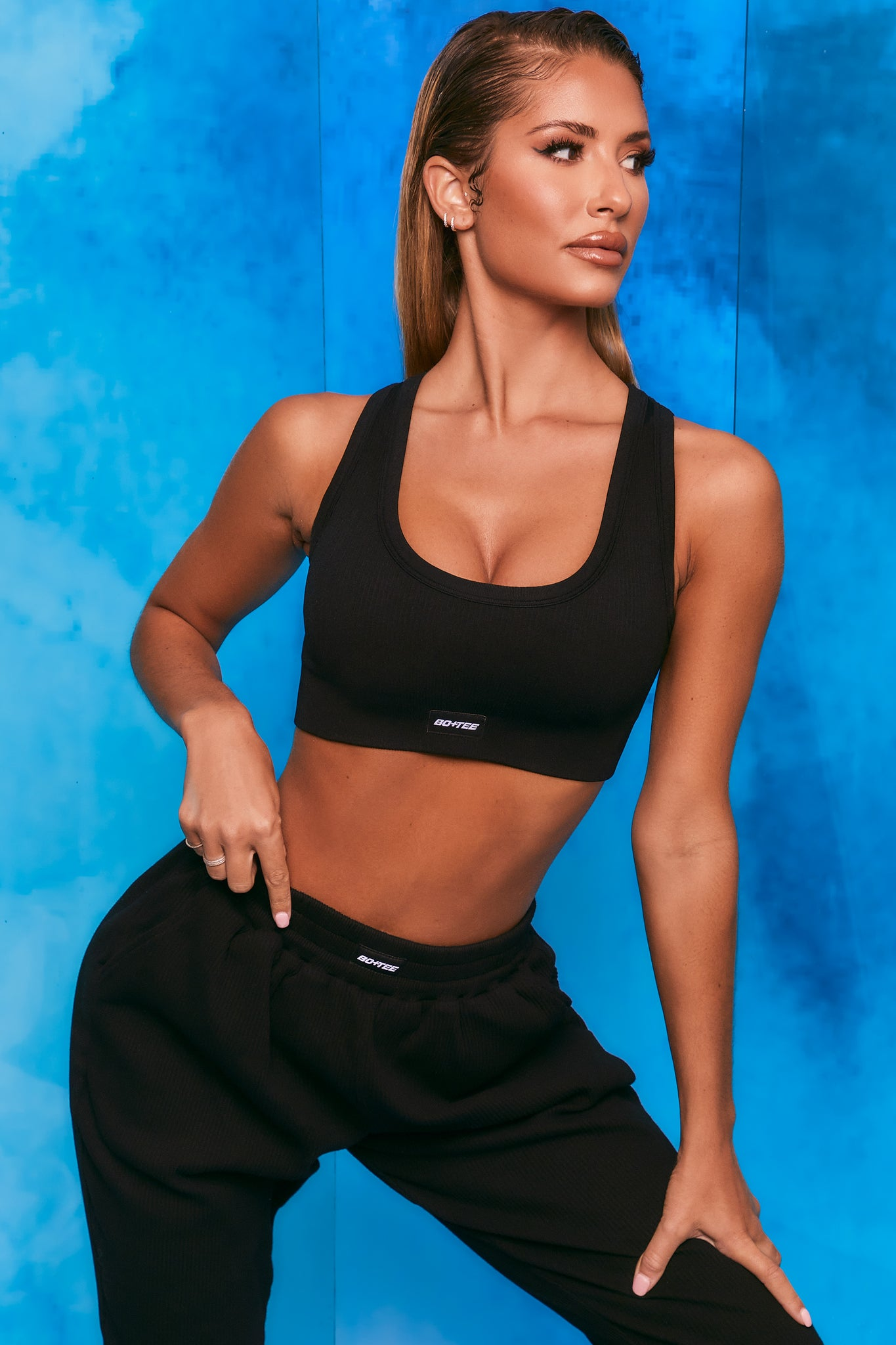 Plain black ribbed scoop neck sports bra. Image 5 of 6