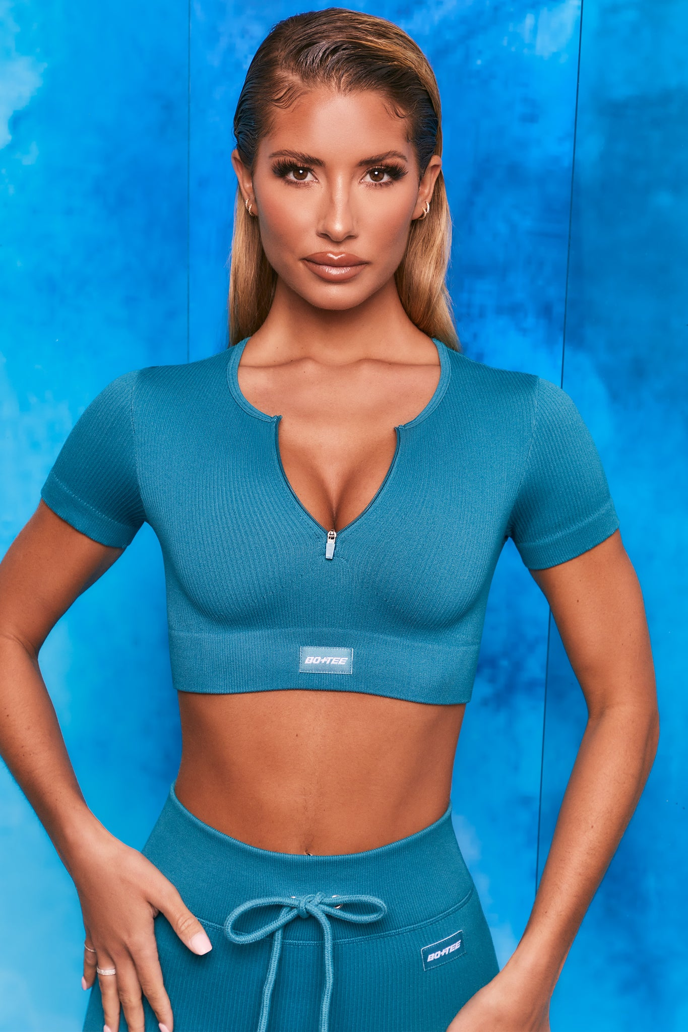 Plain teal notch neck crop top with zip front and short sleeves. Image 1 of 6