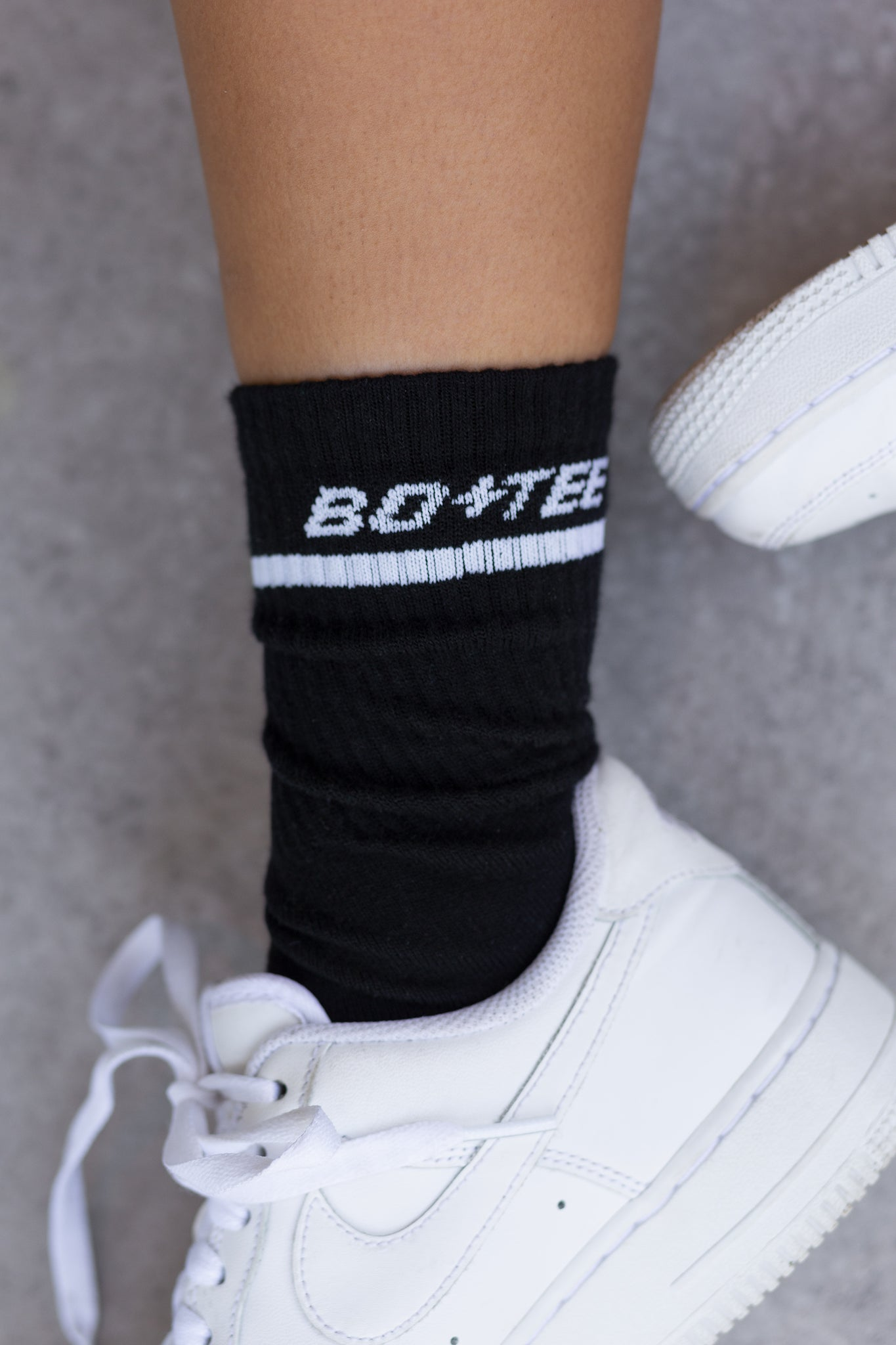 Black ribbed ankle socks with stitched logo branding and stripe edge. Image 5 of 6.