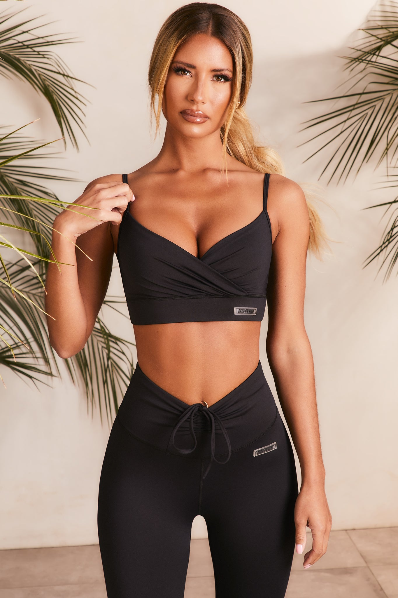 Slinky plunge neck sports bra in black with ruched wrap front. Image 1 of 6.