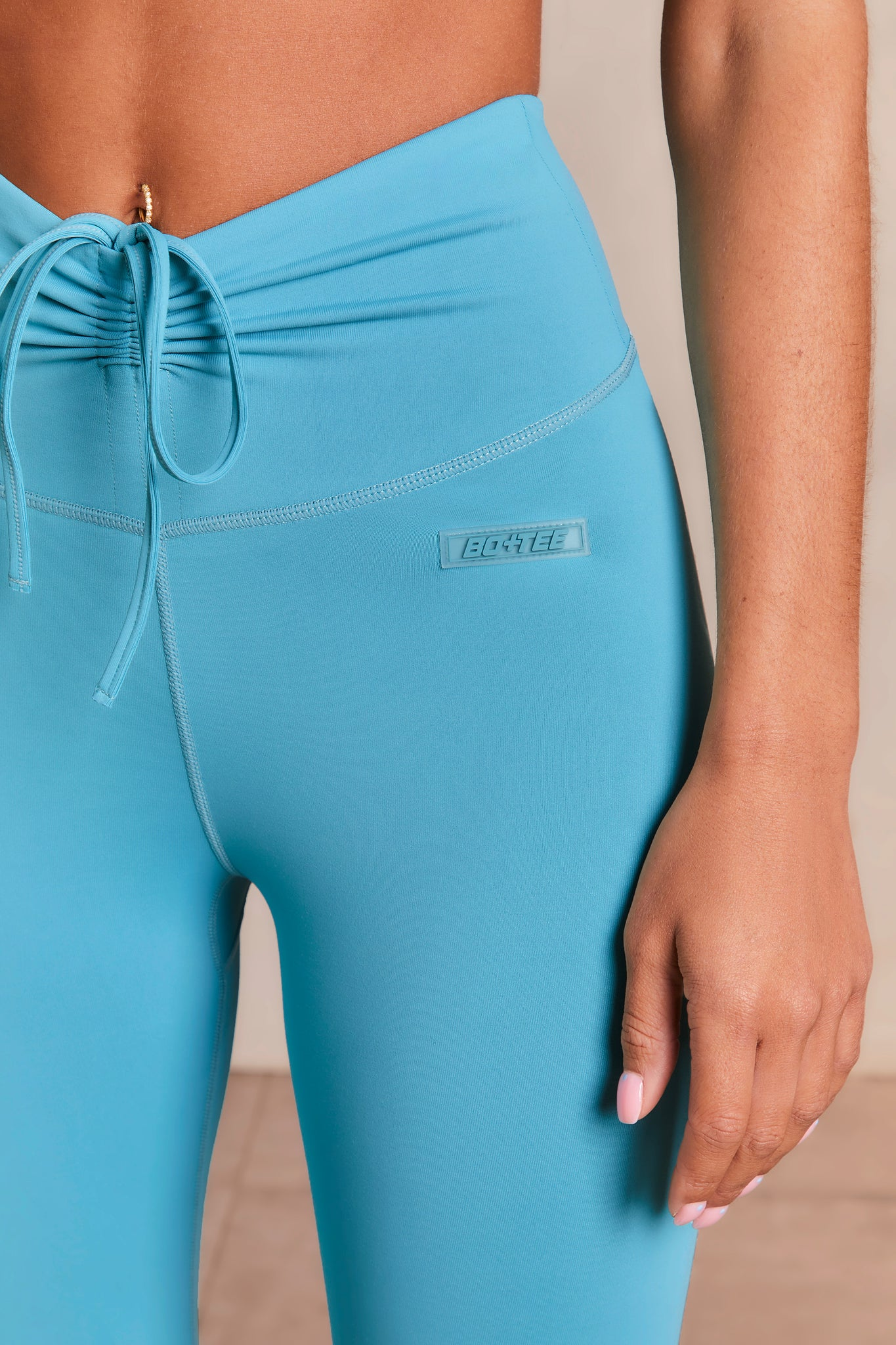 Slinky leggings in aqua with V shaped high waist and tie front. Image 5 of 6