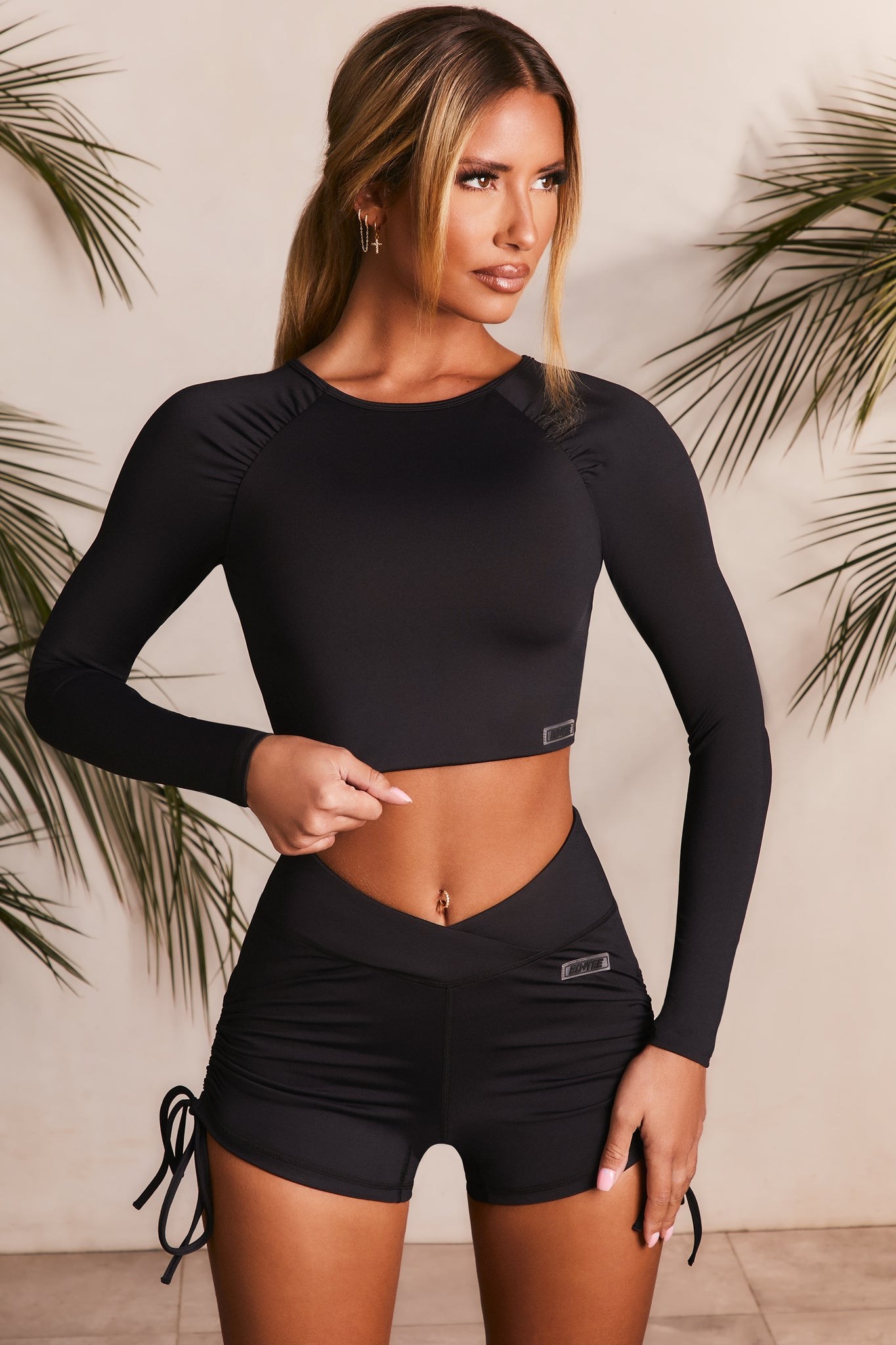 Slinky long sleeve crop top in black with round neck. Image 1 of 6.
