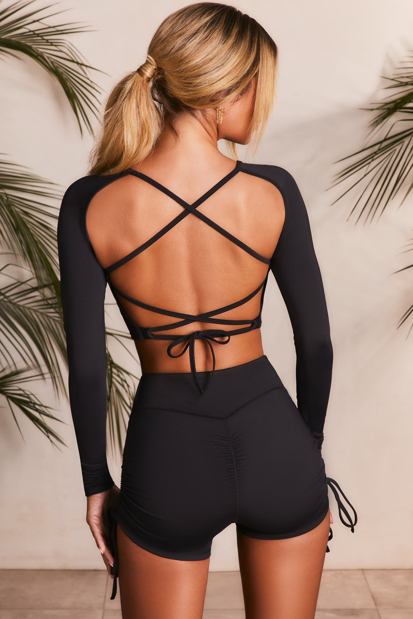 Slinky long sleeve crop top in black with an open back and cross ties Image 3 of 6.