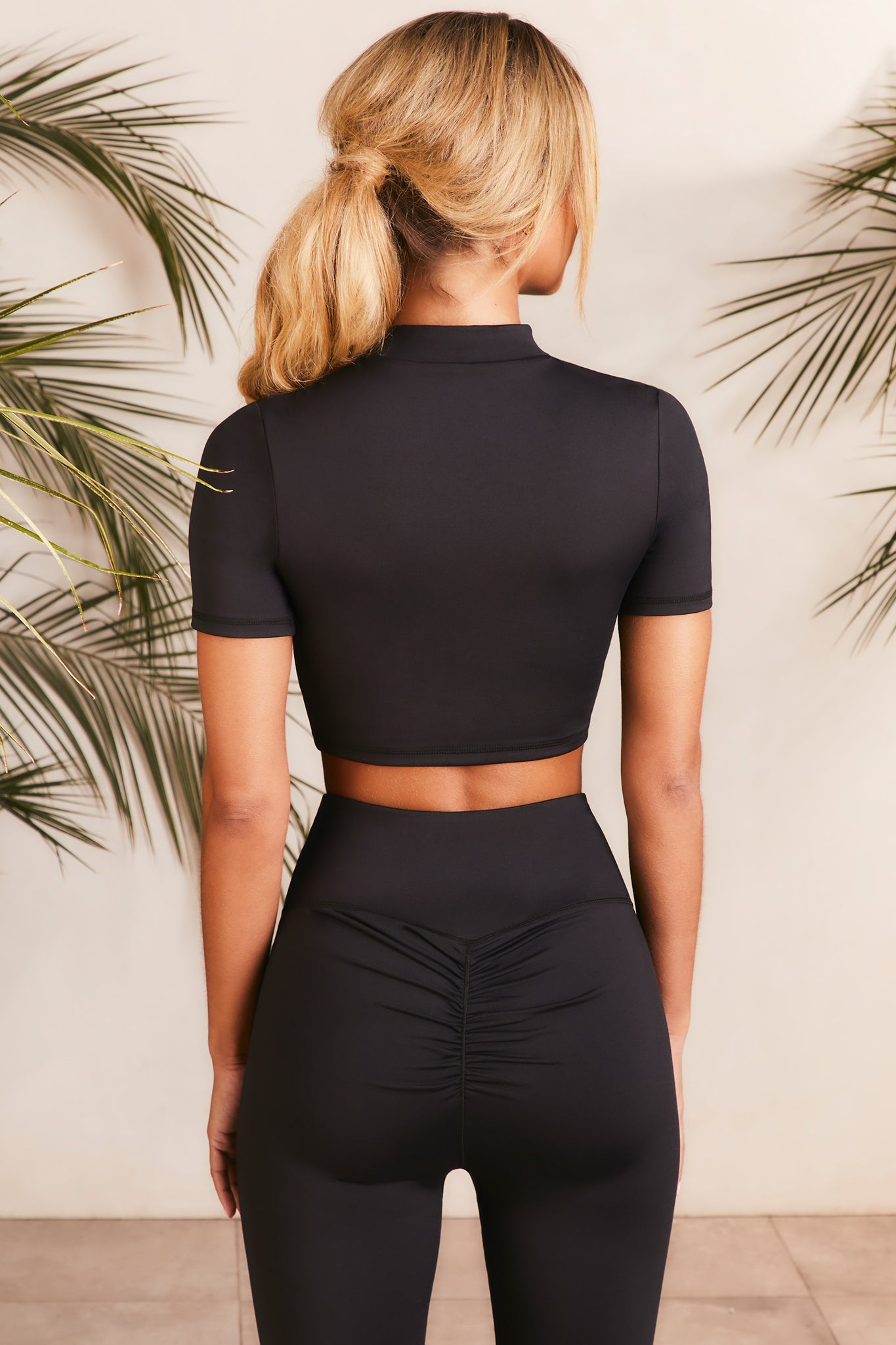 High neck crop top in black with short sleeves. Image 3 of 6.