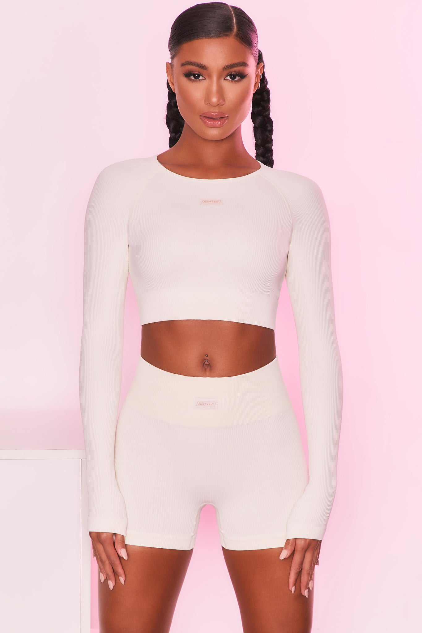Ribbed long sleeve crop top in cream with round neckline and central logo branding. Image 5 of 6.