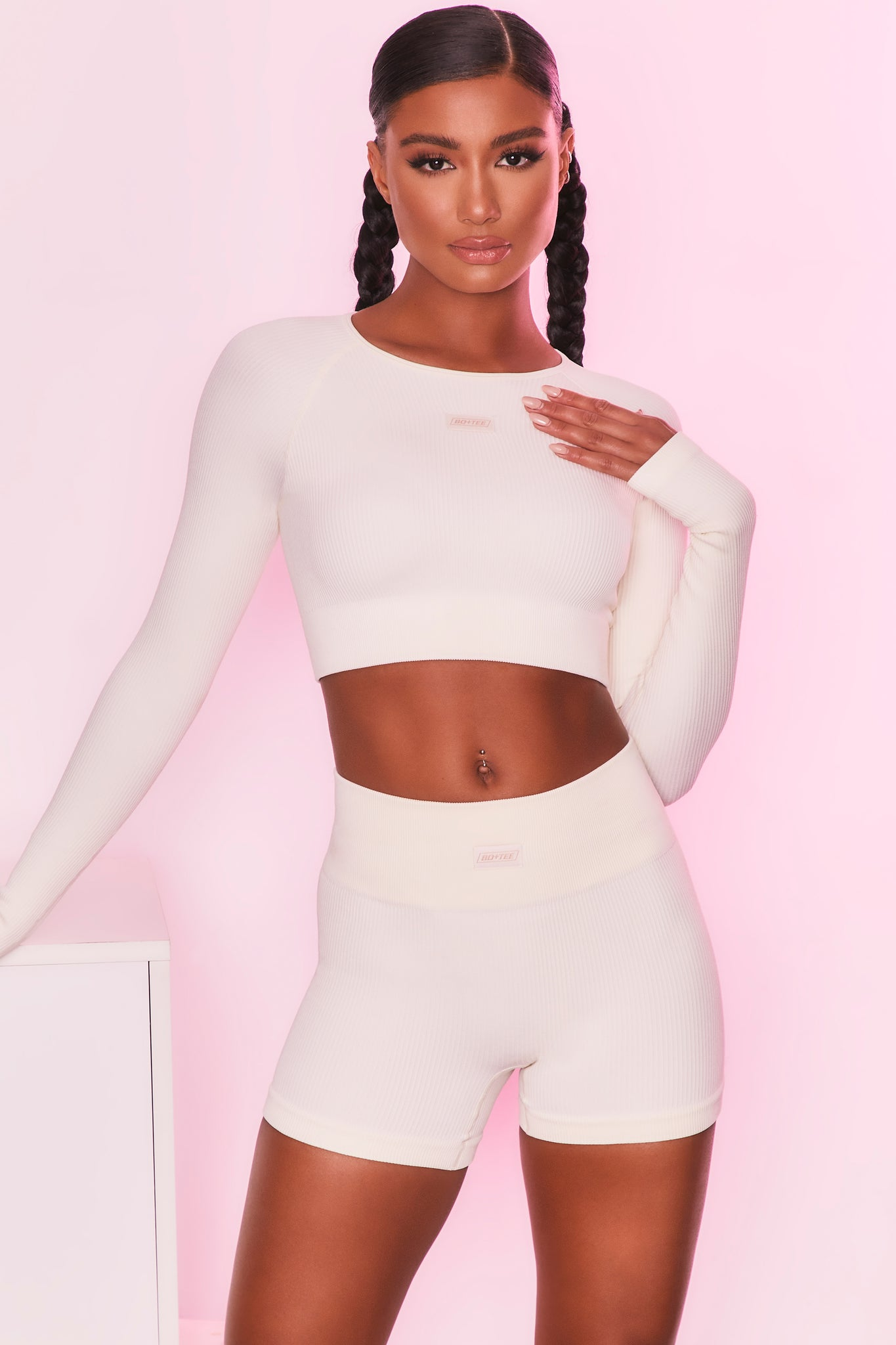 Ribbed long sleeve crop top in cream with round neckline and central logo branding. Image 6 of 6.