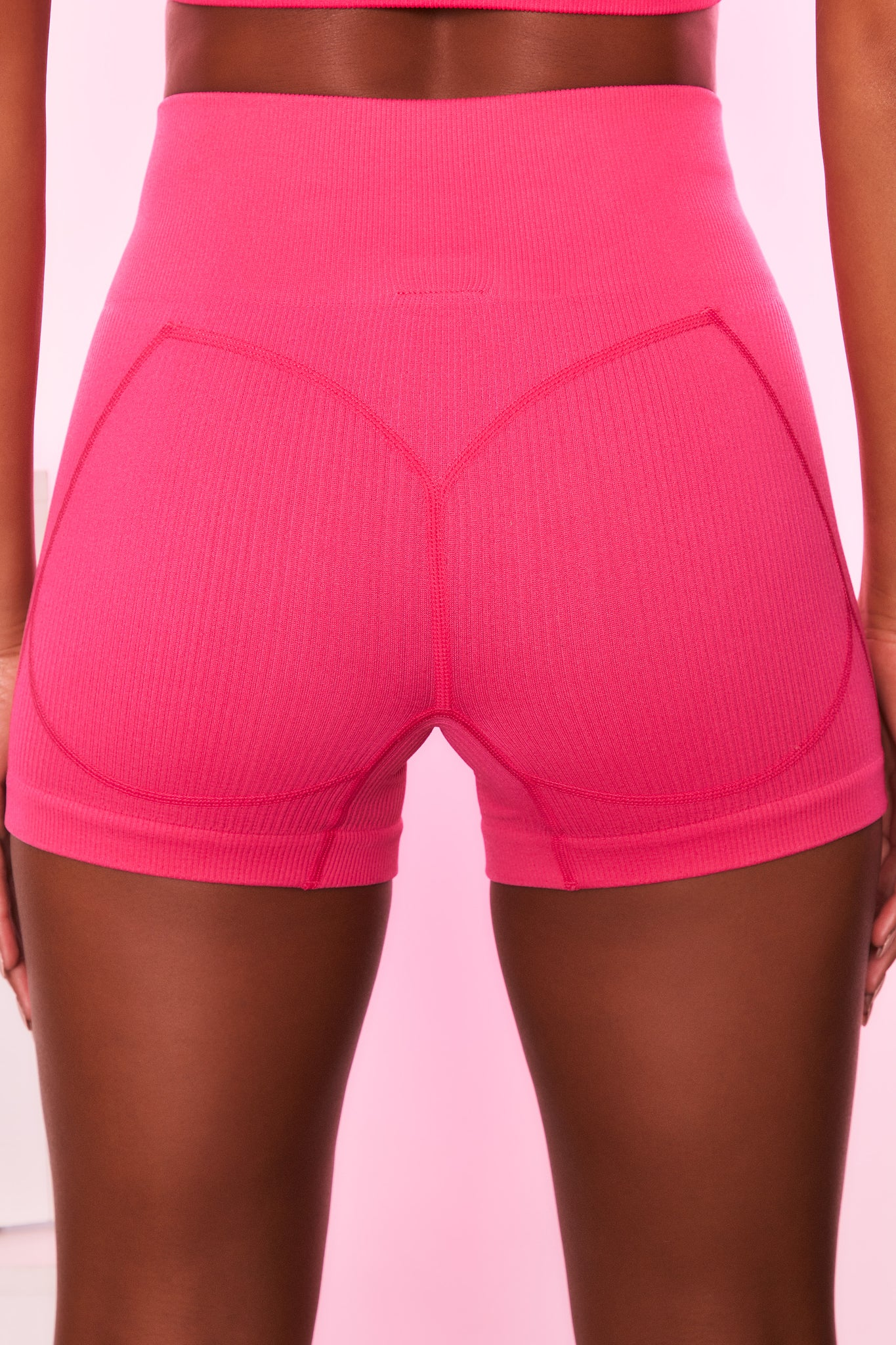 High waisted ribbed mini shorts in hot pink with seam detailing. Image 3 of 6.