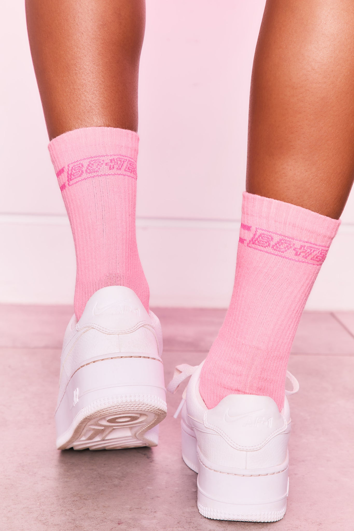Ribbed ankle socks in coral with logo branding on the back. Image 1 of 4.