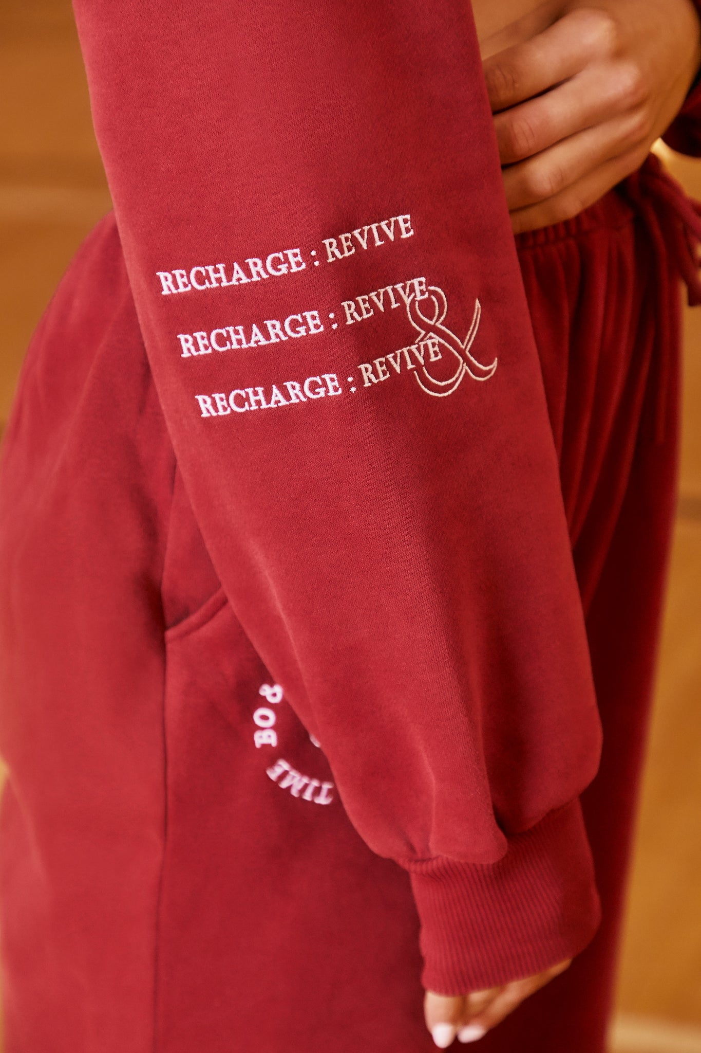 Burgundy long sleeve cropped sweatshirt with drawstring tie hem and logo branding on the arm. Image 5 of 6.