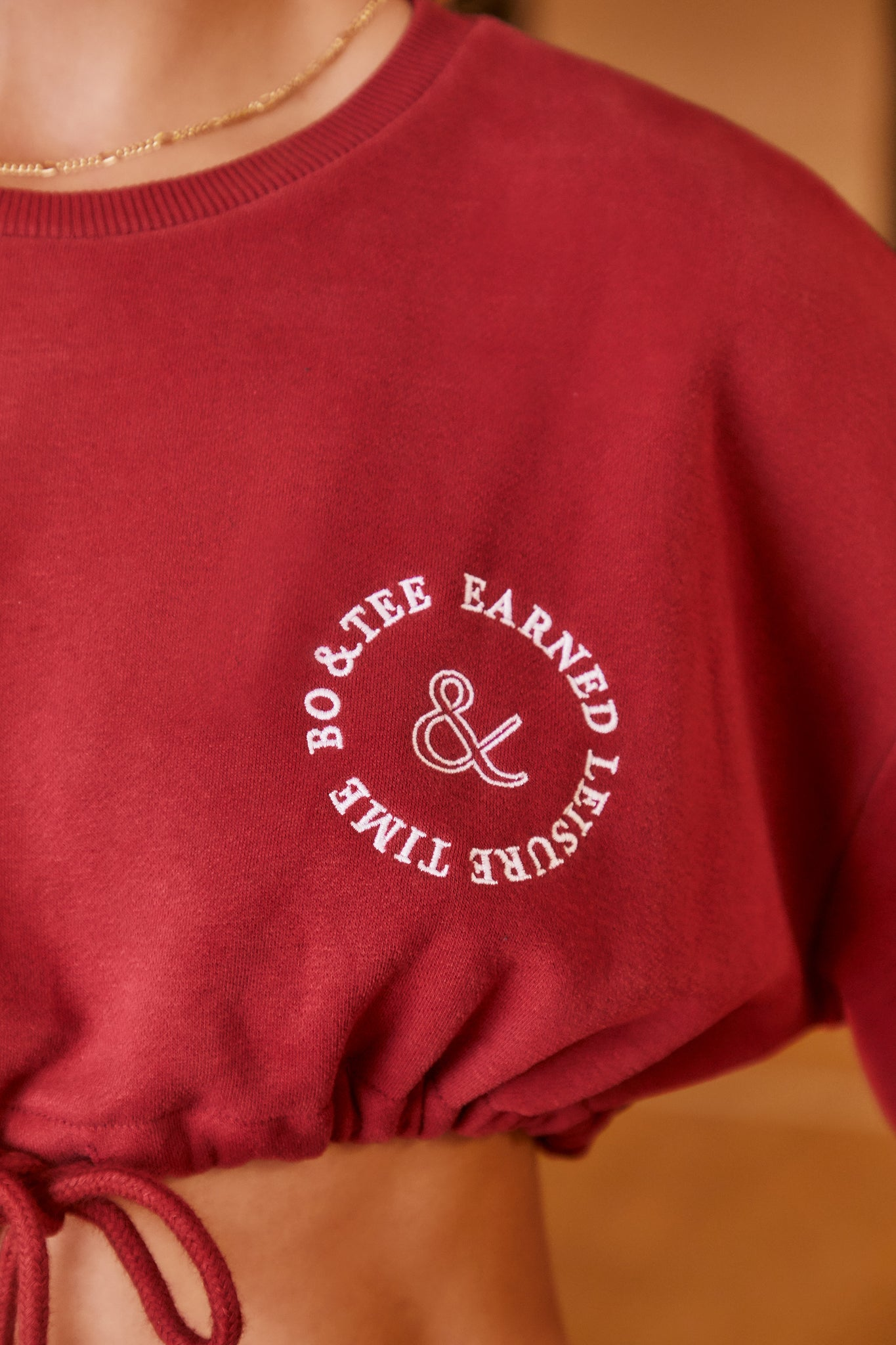 Burgundy long sleeve cropped sweatshirt with drawstring tie hem and logo branding on the chest. Image 4 of 6.