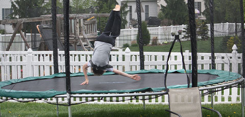 a boy is doing backflip on large trampoline