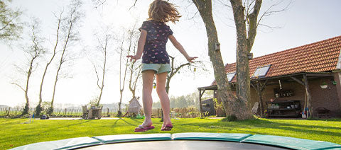 kids jumping on a commercial trampoline in the backyard