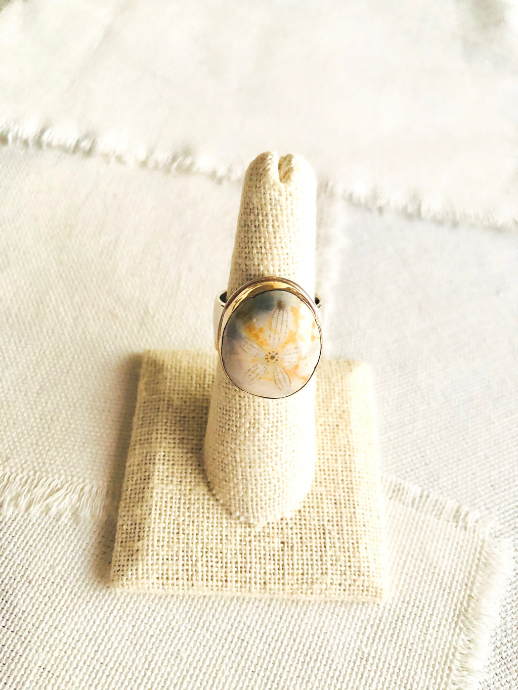 Who would think fossil jewelry would be so beautiful and feminine?  This fossilized sea urchin ring is bezel set in 14 kt gold and soldered to a sterling silver back plate and hand hammered shank.