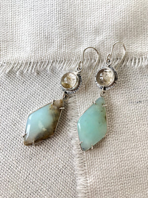 These one of a kind Peruvian blue opal earrings will bring joy and light to any outfit.  These Peruvian Blue Opal earrings are prong set in sterling silver and paired with rutilated quartz stones to continue the soft muted style.