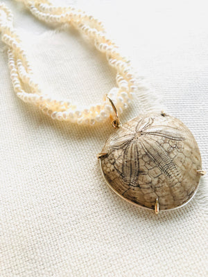 This is a one of a kind artisan made fossilized sand dollar on seed pearls necklace.