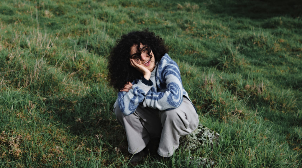 Roxie sits in a grassy field with her face in the palm of her hand, her curly hair partially covers her face.