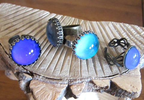 circular mood rings lying on some wood turning blue and purple mood colors