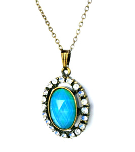 an oval mood pendant necklace with blue mood color and stones around the edges