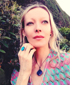 blonde model in the garden wearing a mood ring, a mood necklace and mood earrings