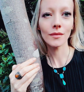 model by a tree wearing a mood necklace and a mood ring