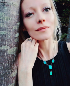 blonde model wearing a bronze mood ring and a mood necklace